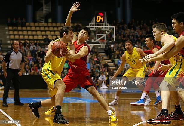 Ben Madgen of Australia looks to pass against XiaoYu Liu of China during the 2014 Sino-Australia Challenge match between the Australian Boomers and...