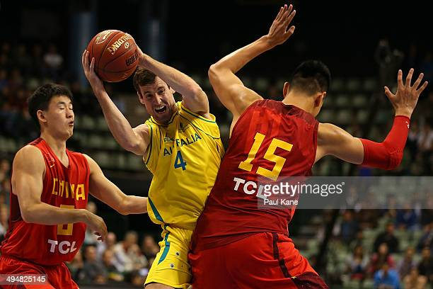 Ben Madgen of Australia passes the ball against Quan Gu and Zhonghao Xu of China during the 2014 Sino-Australia Challenge match between the...