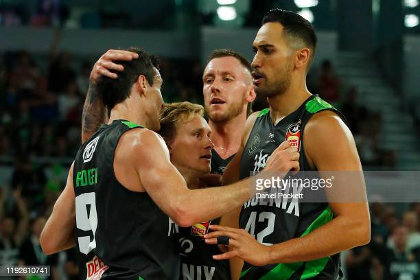 Ben Madgen of the Phoenix celebrates with teammates Kyle Adnam, Mitchell Creek and Tai Wesley during the round 10 NBL match between the South East...