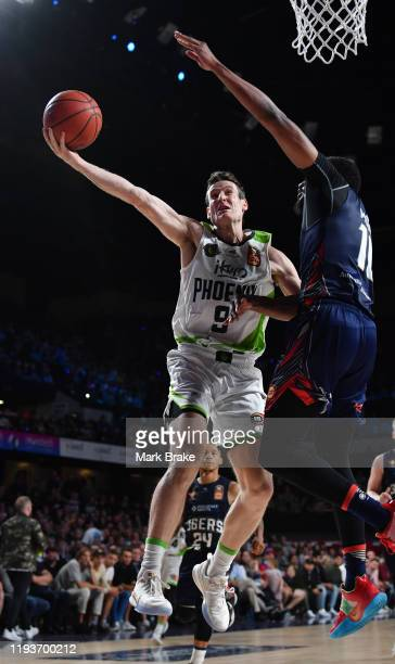 Ben Madgen of the Phoenix heads for the basket defended by Ramone Moore of the 36ers during the round 11 NBL match between the Adelaide 36ers and the...