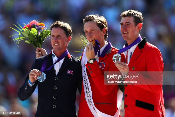Ben Maher of Great Britain or Team GB riding Explosion W poses with the silver medal, Martin Fuchs of Switzerland riding Clooney 51 with the gold...
