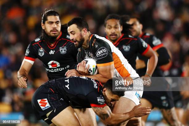 Ben Matulino of the Tigers on the charge against Shaun Johnson of the Warriors during the round nine NRL match between the New Zealand Warriors and...