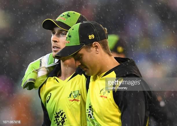Ben McDermott and Alex Carey of Australia walk off the field as rain starts to fall again during the International Twenty20 match between Australia...