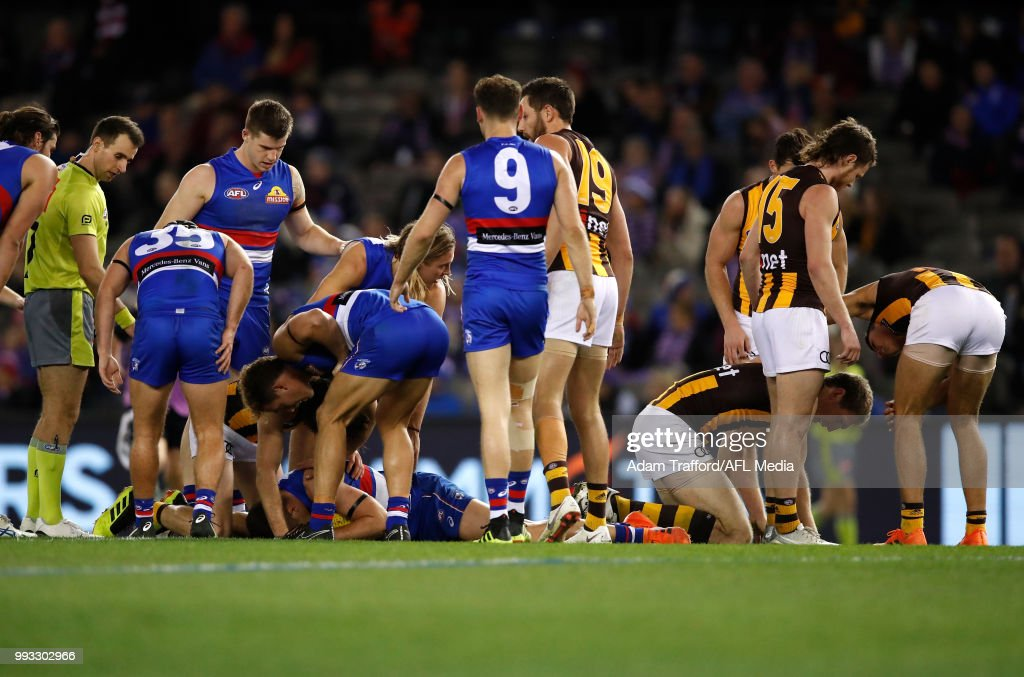 Ben McEvoy of the Hawks and Josh Dunkley of the Bulldogs are seen recovering after a heavy knock during the 2018 AFL round 16 match between the Western Bulldogs and the Hawthorn Hawks at Etihad Stadium on July 07, 2018 in Melbourne, Australia.