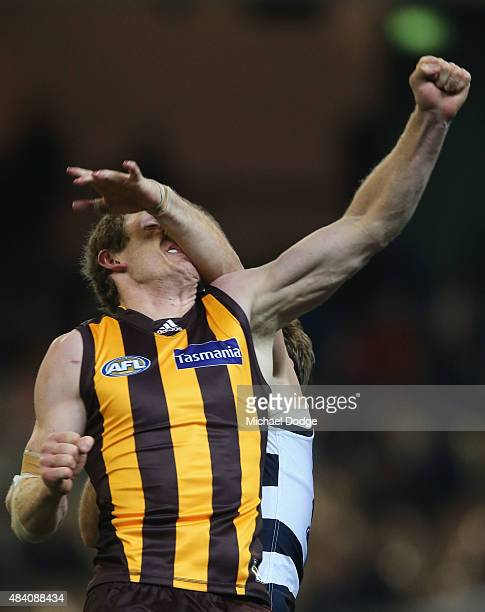 Ben McEvoy of the Hawks cops a hit to the face from Tom Hawkins of the Cats during the round 20 AFL match between the Geelong Cats and the Hawthorn...