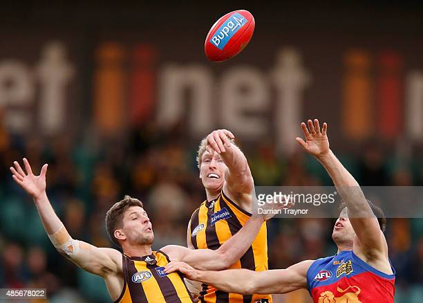 Ben McEvoy of the Hawks taps the ball clear of Stefan Martin of the Lions during the round 22 AFL match between the Hawthorn Hawks and the Brisbane...