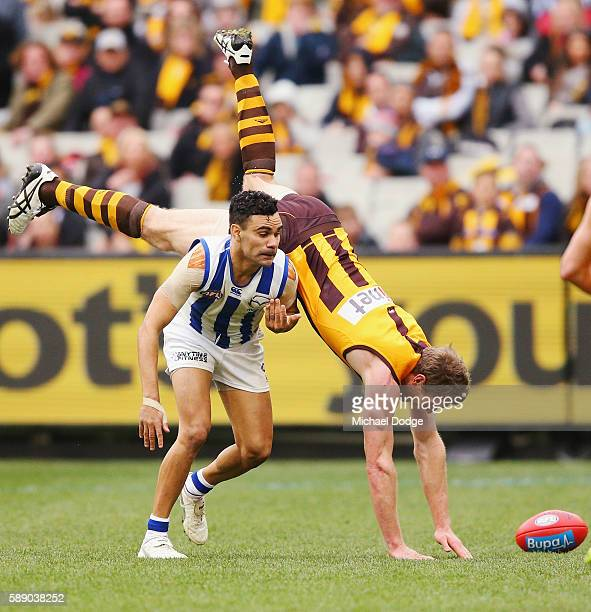 Ben McEvoy of the Hawks tumbles over Lindsay Thomas of the Kangaroos during the round 21 AFL match between the Hawthorn Hawks and the North Melbourne...