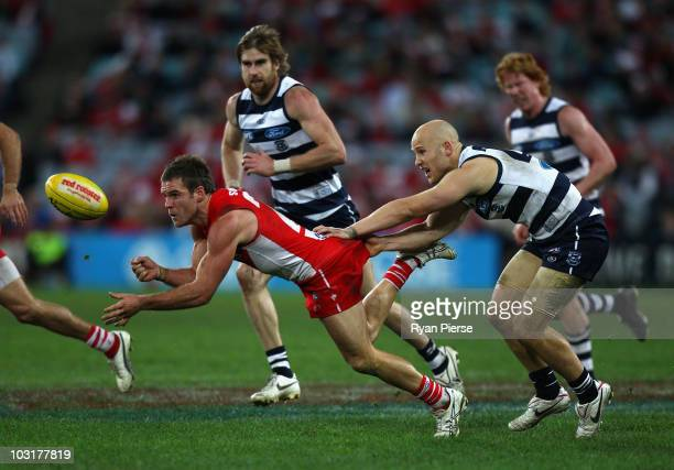 Ben McGlynn of the Swans gets a handball away despite a tackle by Gary Ablett of the Cats during the round 18 AFL match between the Sydney Swans and...