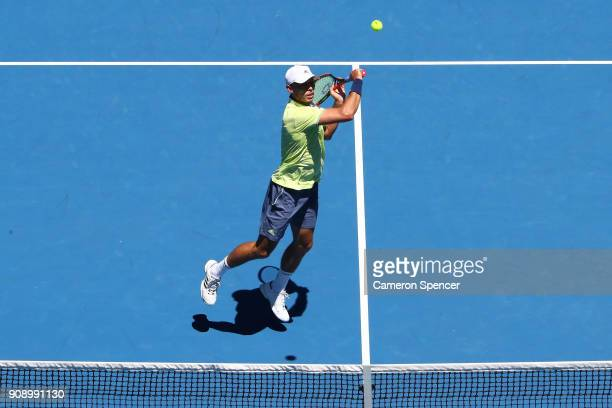 Ben McLachlan of Japan plays a backhand in his fourth round men's doubles match with JanLennard Struff of Germany against Lukasz Kubot of Poland and...