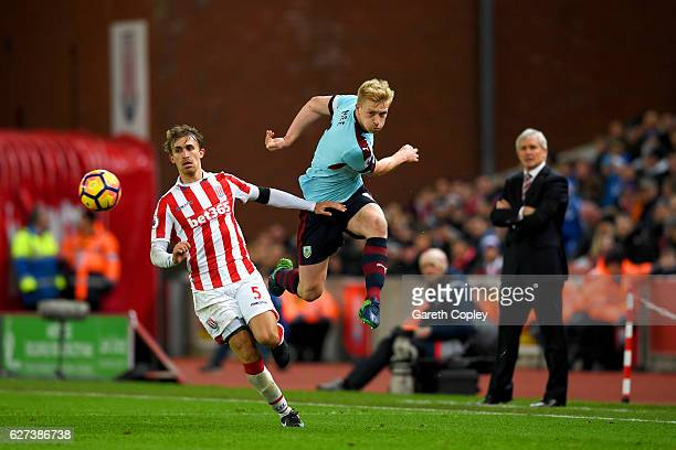 Ben Mee of Burnley and Marc Muniesa of Stoke City compete for the ball during the Premier League match between Stoke City and Burnley at Bet365...