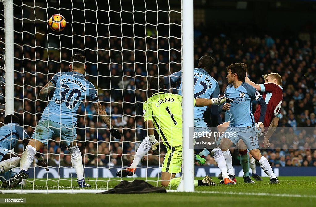Ben Mee of Burnley (R) scores his sides first goal during the Premier League match between Manchester City and Burnley at Etihad Stadium on January 2, 2017 in Manchester, England.