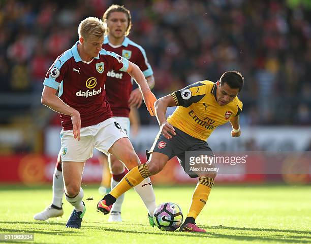 Ben Mee of Burnley tackles Alexis Sanchez of Arsenal during the Premier League match between Burnley and Arsenal at Turf Moor on October 2 2016 in...