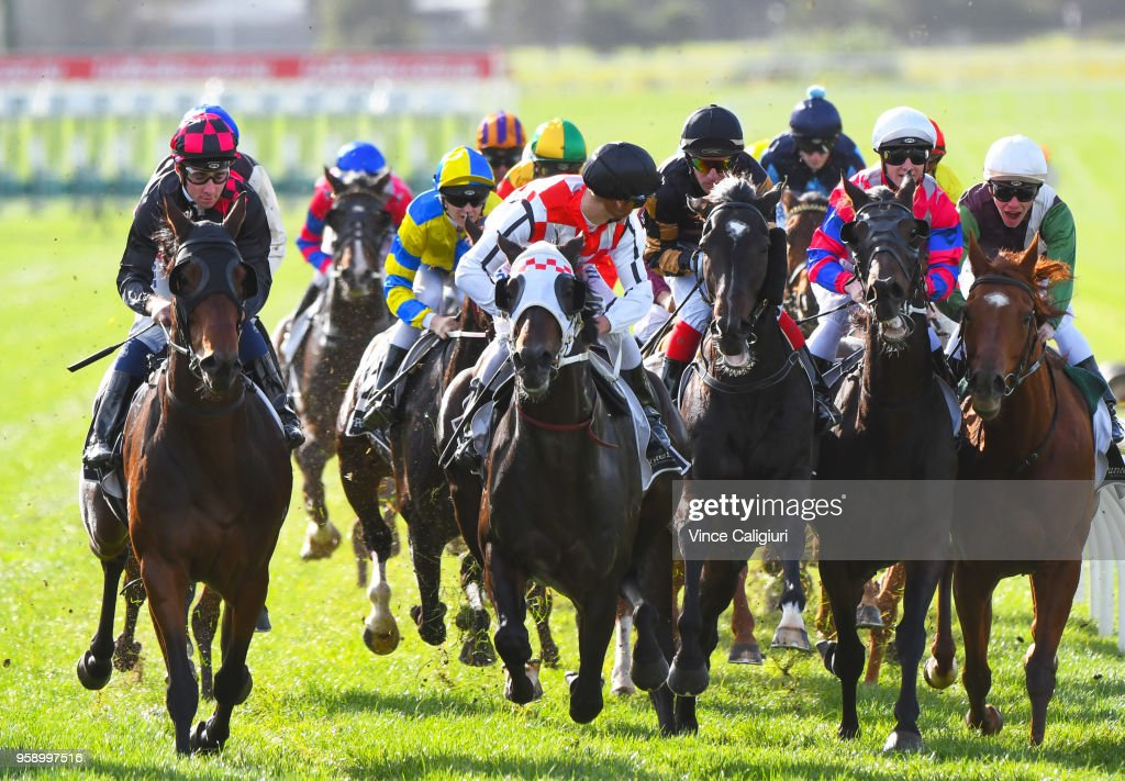 Ben Melham riding Crafty Cruiser, Mitch Aitken riding Zataglio, Dale Smith riding Royal Volley and Regan Bayliss aboard Johnny Vinko (looking over shoulder) approach the the first turn in Race 4 during Melbourne Racing at Sandown Hillside on May 16, 2018 in Melbourne, Australia.