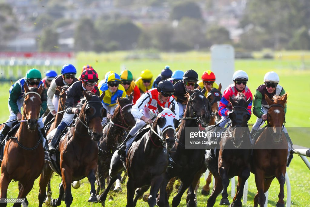 Ben Melham riding Crafty Cruiser, Mitch Aitken riding Zataglio, Dale Smith riding Royal Volley and Regan Bayliss aboard Johnny Vinko approach the the first turn in Race 4 during Melbourne Racing at Sandown Hillside on May 16, 2018 in Melbourne, Australia.