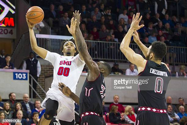 Ben Moore of the SMU Mustangs drives to the basket against Ernest Aflakpui and Obi Enechionyia of the Temple Owls during a basketball game on January...