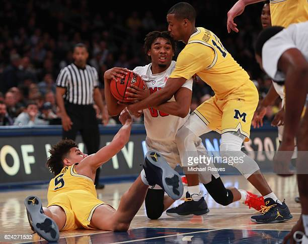 Ben Moore of the Southern Methodist Mustangs fights for a loose ball with DJ Wilson and MuhammadAli AbdurRahkman of the Michigan Wolverines in the...