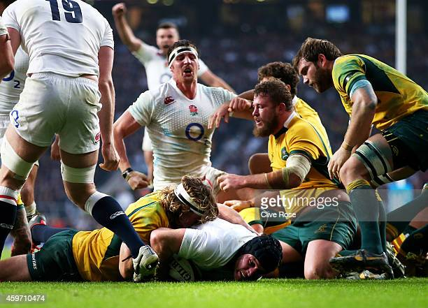 Ben Morgan of England crashes through the tackle from Michael Hooper of Australia to score his team's second try during the QBE international match...