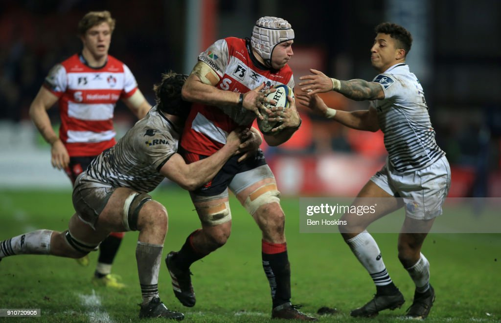 Ben Morgan of Gloucester is tackled by James Ratti and Jay Baker of Ospreys during the Anglo-Welsh Cup match between Gloucester Rugby and Ospreys at Kingsholm Stadium on January 26, 2018 in Gloucester, England.