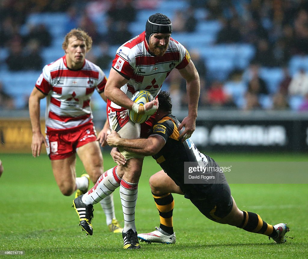 Ben Morgan of Gloucestser is tackled by Carlo Festuccia during the Aviva Premiership match between Wasps and Gloucester at The Ricoh Arena on November 8, 2015 in Coventry, England.