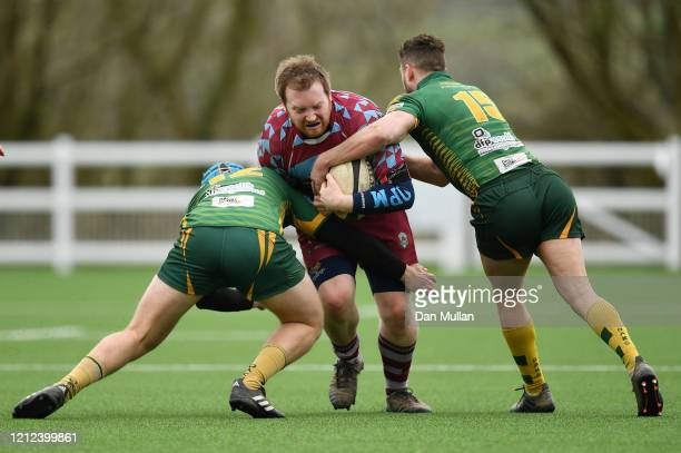 Ben Neville of OPMs is tackled by Alex Broughton and Hayden Coles of Plymstock Albion Oaks during the Lockie Cup Semi Final match between Old...
