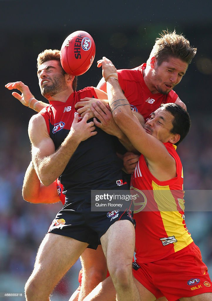 Ben Newton of the Demons marks infront of Greg Broughton of the Suns and Jesse Hogan of the Demons during the round one AFL match between the Melbourne Demons and the Gold Coast Suns at Melbourne Cricket Ground on April 4, 2015 in Melbourne, Australia.