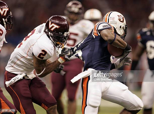 Ben Obomanu of the Auburn Tigers is grabbed by Jimmy Williams of the Virginia Tech Hokies during a broken play at the Nokia Sugar Bowl on January 3...