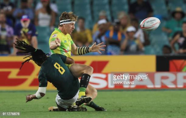 Ben O'Donnell of Australia passes the ball as he is tackled by Rosko Specman of South Africa in the final during day three of the Sydney World Rugby...