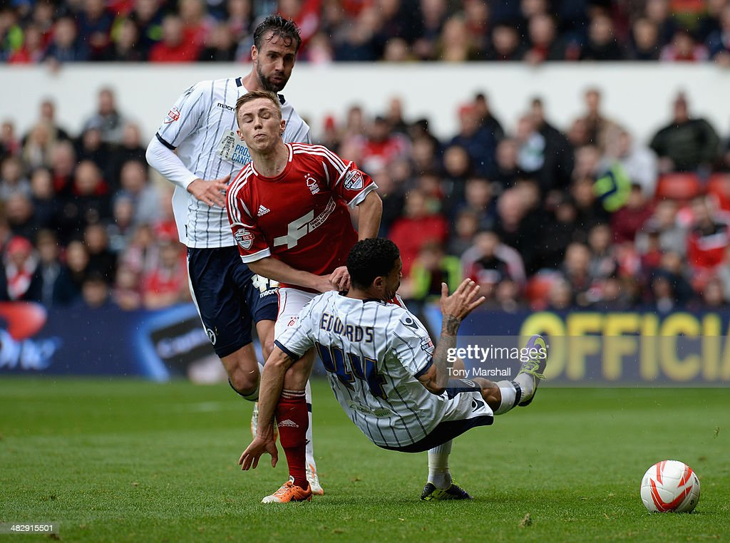 Ben Osborn of Nottingham Forest tackled by Carlos Edwards of Millwall during the Sky Bet Championship match between Nottingham Forest and Millwall at City Ground on April 05, 2014 in Nottingham, England,