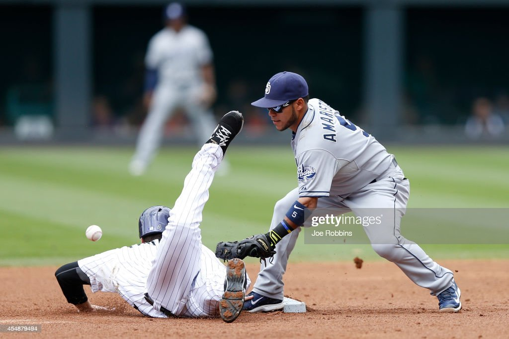 Ben Paulsen #4 of the Colorado Rockies dives back to second base ahead of the throw to Alexi Amarista #5 of the San Diego Padres in the second inning of the game at Coors Field on September 7, 2014 in Denver, Colorado.