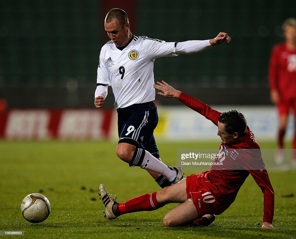 Ben Payal of Luxembourg tackles Kenny Miller of Scotland during the International Friendly match between Luxembourg and Scotland at Stade Josy Barthel on November 14, 2012 in Luxembourg, Luxembourg.