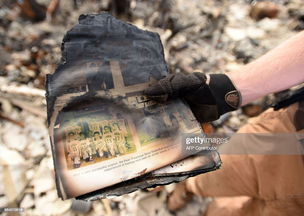 Ben Pedersen displays his partially burned high school yearbook that he found at his burned home in the Coffey Park area of Santa Rosa, California, on October 20, 2017. Residents are being allowed to return to their burned homes on October 20 to grieve and search through remains. Around 5,700 homes and businesses have been destroyed by the fires, the deadliest in California's history. /