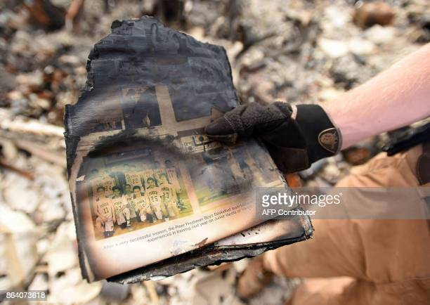 Ben Pedersen displays his partially burned high school yearbook that he found at his burned home in the Coffey Park area of Santa Rosa California on...