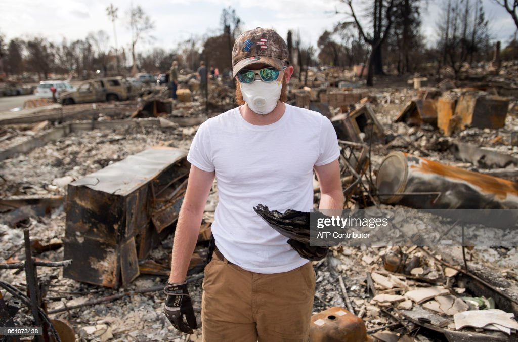 Ben Pedersen poses for a photo with his partially burned high school yearbook that he found at his burned home in the Coffey Park area of Santa Rosa, California, on October 20, 2017. Residents are being allowed to return to their burned homes on October 20 to grieve and search through remains. Around 5,700 homes and businesses have been destroyed by the fires, the deadliest in California's history. /