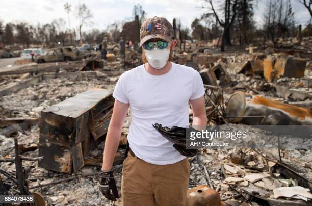 Ben Pedersen poses for a photo with his partially burned high school yearbook that he found at his burned home in the Coffey Park area of Santa Rosa...