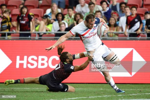 Ben Pinkelman of USA fends off a challenge from Dan Bibby of England during the 2018 Singapore Sevens Pool B match between USA and England at...