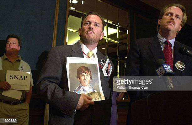 Ben Poliser holds a Survivors Network of those Abused by Priests sign as his cousin Mark Serrano board member of SNAP holds a picture of himself as a...