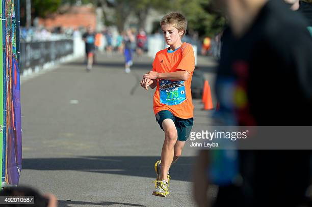 Ben Rees 14 years old crosses the finish line of the 1/2 marathon with a time of 1:34:30 during the 9th annual Colfax Marathon May 18, 2014. The 26.2...