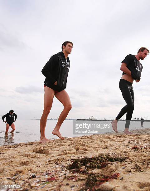 Ben Reid and Lachlan Keeffe of the Magpies walk out of the water during a Collingwood Magpies AFL recovery session at St Kilda Beach on July 14 2014...