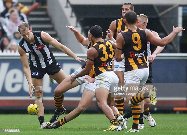 Ben Reid of the Magpies jumped for a high mark over David Hale of the Hawks but sustains a leg injury here when landing on his right leg during the...