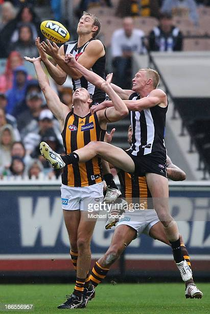 Ben Reid of the Magpies jumps for a high mark over David Hale of the Hawks but sustains a leg injury when landing on his right leg during the round...