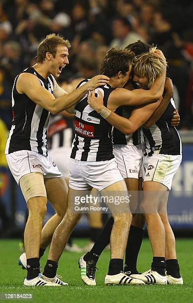 Ben Reid, Steele Sidebottom, Harry O'Brien and Dale Thomas of the Magpies celebrate winning the first preliminary final match between the Collingwood...
