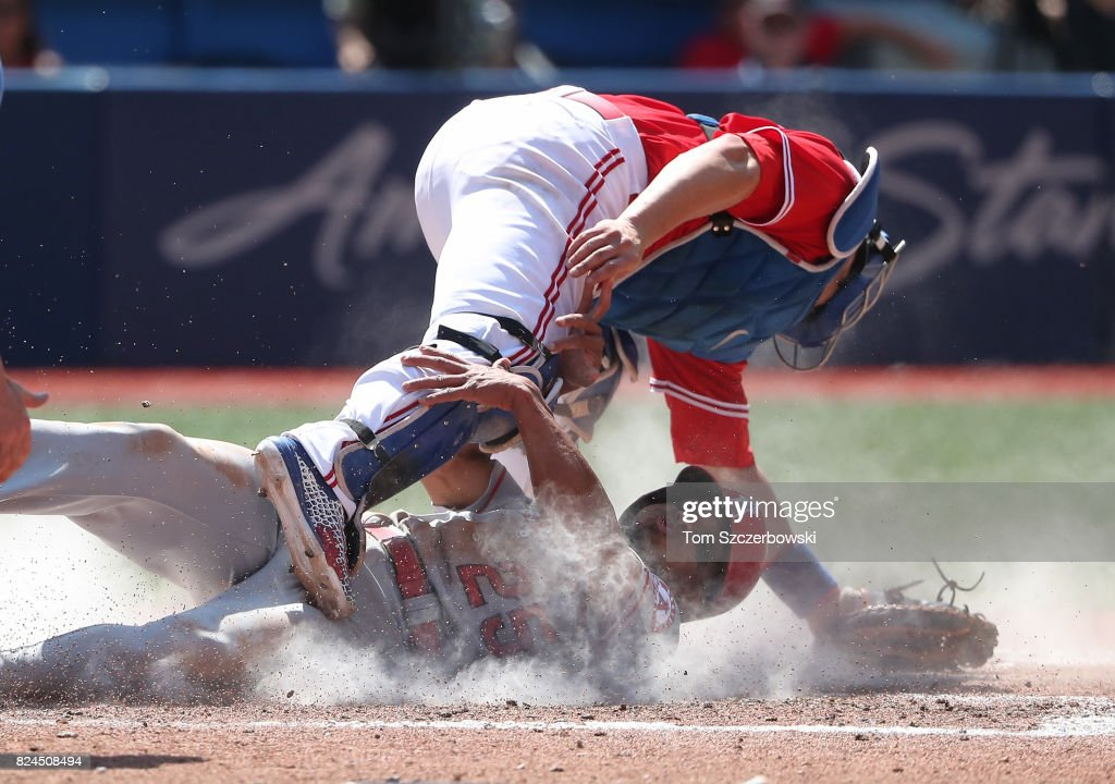 Ben Revere #25 of the Los Angeles Angels of Anaheim slides safely into home plate to score on a sacrifice fly in the fifth inning during MLB game action as Miguel Montero #47 of the Toronto Blue Jays falls after colliding with Revere at Rogers Centre on July 30, 2017 in Toronto, Canada.