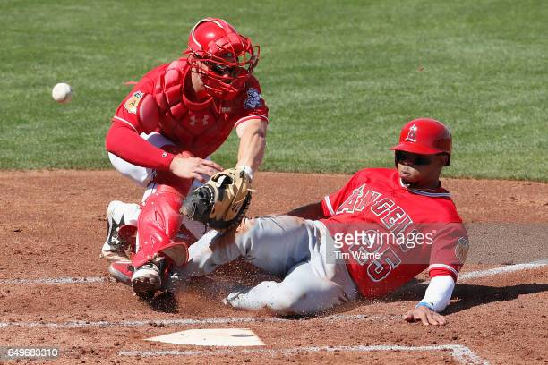 Ben Revere of the Los Angeles Angels slides into home as Rob Brantly of the Cincinnati Reds cannot field the throw in the second inning during the...