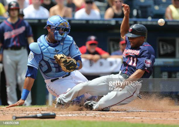 Ben Revere of the Minnesota Twins slides into home safely as Salvador Perez of the Kansas City Royals waits for the throw in the third inning at...