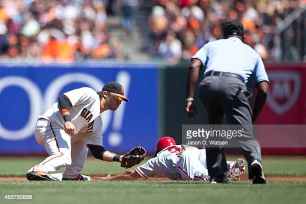 Ben Revere of the Philadelphia Phillies is tagged out attempting to steal second base by Brandon Crawford of the San Francisco Giants in front of...