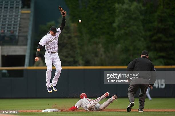 Ben Revere of the Philadelphia Phillies slides safely into second base with a steal as Troy Tulowitzki of the Colorado Rockies leaps but is unable to...