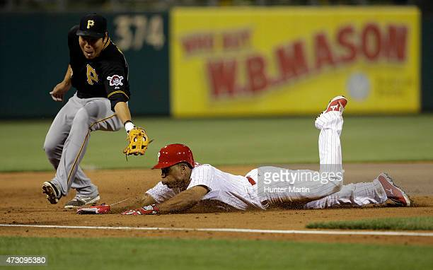 Ben Revere of the Philadelphia Phillies slides safely into third base as Jung Ho Kang of the Pittsburgh Pirates attempts to make the tag in the sixth...