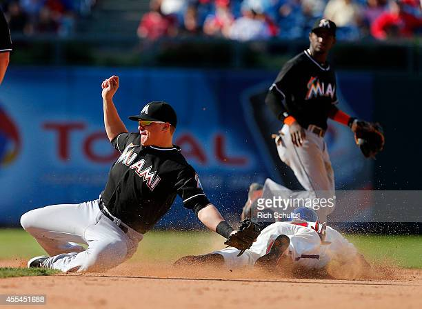 Ben Revere of the Philadelphia Phillies steals second base as the ball sails past Enrique Hernandez of the Miami Marlins allowing Revere to advance...