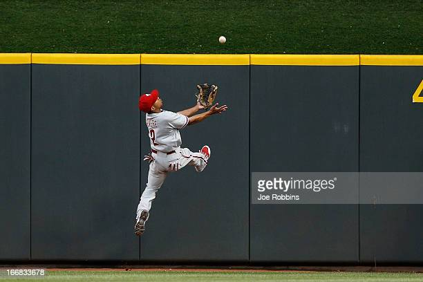Ben Revere of the Philadelphia Phillies tries to make a play at the wall on a ball hit by Mike Leake of the Cincinnati Reds during the game at Great...