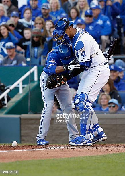 Ben Revere of the Toronto Blue Jays and Salvador Perez of the Kansas City Royals react at home plate after the ball bounces off of Revere's helmet in...